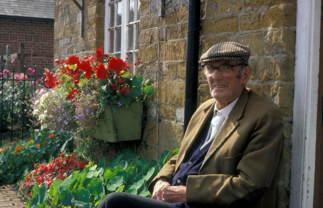Smiling elderly man sitting in his cottage garden UK